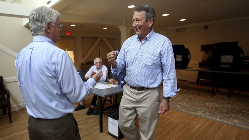 Poll volunteer Tom Spain hands out stickers to former Gov, Mark Sanford after he cast his own ballot
