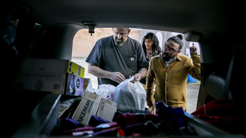 Mark Lane, left, of the Minority Humanitarian Foundation hands out supplies at a migrant shelter in the Matamoros neighborhood in Tijuana.