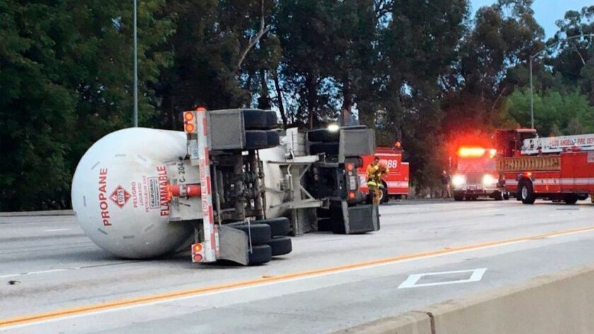 A tanker truck hauling liquid propane is overturned on the 405 Freeway in the San Fernando Valley on Sunday morning. It was blocking all southbound lanes just north of the 101 Freeway interchange.