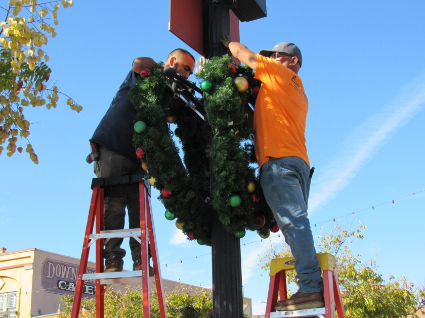 Andreas Vallejo (left) and Martin Sanchez affix a pair of wreaths to a city of El Cajon sign along Main Street near Prescott Promenade on Friday, Nov. 15, in anticipation of the upcoming Mother Goose Parade and the December holidays.