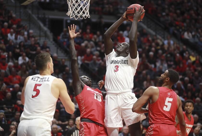 SDSU forward Aguek Arop (3) shoots over New Mexico's Makuach Maluach in a Feb. 11 game against New Mexico at Viejas Arena.