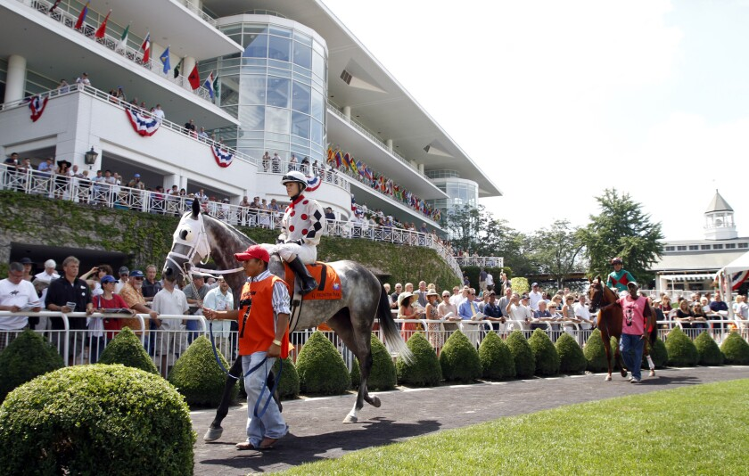 FILE - In this Aug. 21, 2010, file photo, jockey Inez Karlsson, left, is led to the track on Exchanging Kisses before the fourth race prior to the 28th running of the Arlington Million horse race at Arlington Park in Arlington Heights, Ill. The racetrack is expected to close after the completion of racing on Sept. 25, with ownership taking bids for the future of the land. (AP Photo/John Smierciak, File)