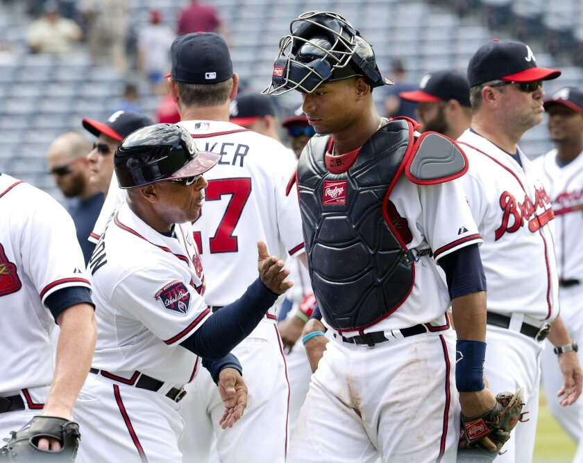 Atlanta Braves catcher Christian Bethancourt (25) is greeted by Atlanta Braves first base coach Terry Pendleton (9) as he leaves the field after defeating the Philadelphia Phillies 7-4 in a baseball game Wednesday, Sept. 3, 2014, in Atlanta. (AP Photo/John Bazemore)