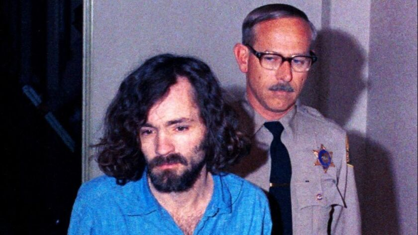 """Charles Manson, head of the cultic """"Manson Family,"""" is escorted by deputy sheriffs on his way to cou"""