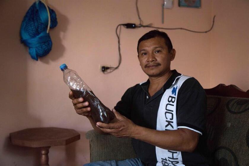 Fotografía del 9 de enero de 2019, del campesino José Luis Tzuc Canté mostrando un recipiente de agua contaminada, recolectada en las cercanias de una granja de cerdos, en la zona de Kenchil en el estado de Yucatán (México). EFE