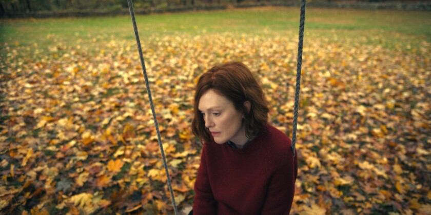 A woman looking downcast while sitting on a swing, surrounded by yellow fallen leaves