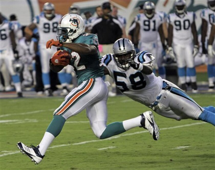 Miami Dolphins running back Reggie Bush (22) carries the ball as Carolina Panthers linebacker Thomas Davis (58) attempts to make the tackle during the first half of an NFL preseason football game, Friday, Aug. 19, 2011, in Miami. (AP Photo/J. Pat Carter)