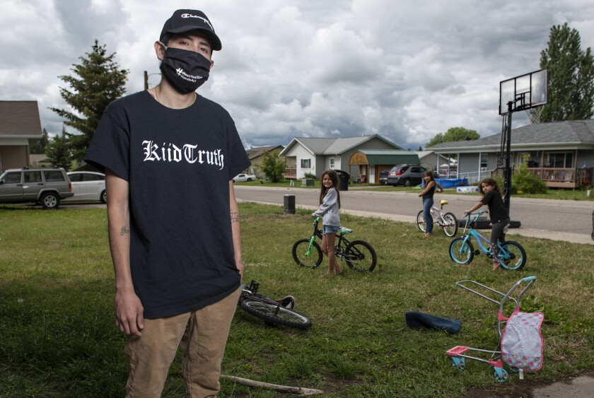 """In this photo taken June 16, 2020, Artie Mendoza III, 25, also known as KiidTruth, looks on outside his home in Pablo, Montana. Mendoza created a viral TIk Tok dance and song to promote hand washing, mask wearing and social distancing among the youth on the Flathead Indian Reservation. Mendoza's children inspired him to create the dance. """"And so I put two and two together, I am aiming for our youth, why not make a fun dance too."""" he said. (AP Photo/Tommy Martino)"""