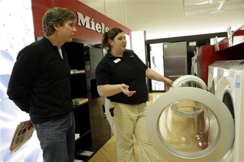 Best Buy associate Verzine Housapyan, right, showcases Miele Energy Star washer and dryer to customer Spyros Skouras at a  Best Buy store in Los Angeles in April. California plans to expand its list of appliances available for energy rebates.