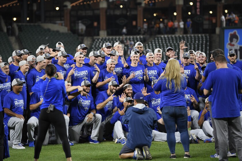 Dodgers pose for photos on the field after beating the Baltimore Orioles on Tuesday in Baltimore. The Dodgers won 7-3, clinching their seventh consecutive NL West title.