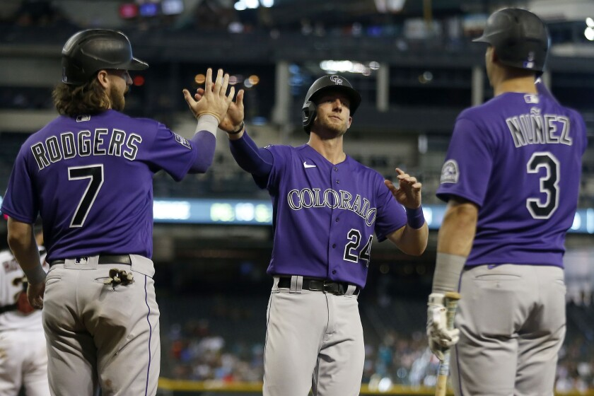 Colorado Rockies' Ryan McMahon (24) is greeted at home plate by Brendan Rodgers (7) and Dom Nuñez (3) after scoring against the Arizona Diamondbacks during the seventh inning of a baseball game Thursday, July 8, 2021, in Phoenix. (AP Photo/Darryl Webb)