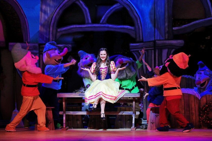 """Olivia Sanabia in the lead role in """"A Snow White Christmas,"""" surrounded by people in dwarf costumes."""