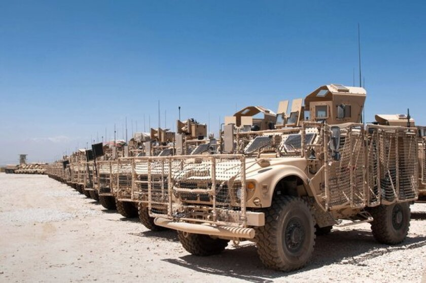 U.S. military vehicles sit in a yard at the Kandahar Airfield in Afghanistan, ready to be shipped back to the United States or other locations.