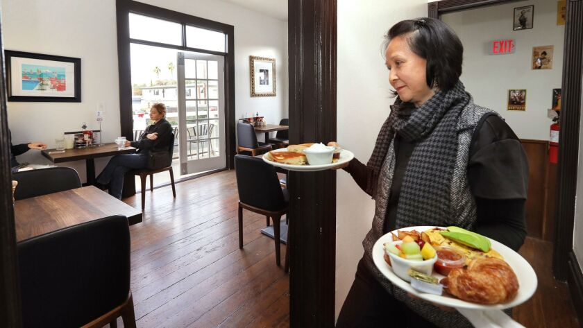Ingrid Thomson, co-manager of the St. Tropez Bistro & Beyond, brings breakfast to customers in one of the place's upstairs dining areas. It's in an old Victorian home on S. Coast Highway in Oceanside.