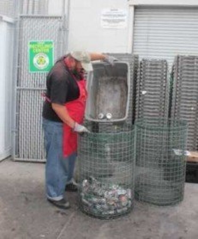 A volunteer helped Tresha Souza out at her recycling center behind the CVS Pharmacy in Pacific Beach, before the city forced Souza to cease operations.