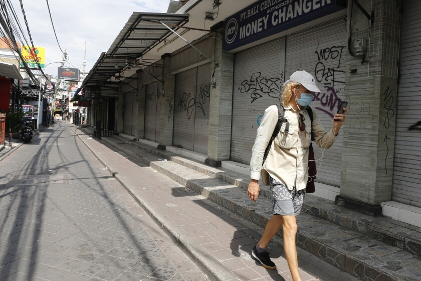 FILE - In this April 14, 2020, file photo, a foreign tourist walks along an empty road lined with closed shops in Bali, Indonesia. The Asian Development Bank has forecast Tuesday, Sept. 15, 2020 that developing economies in the region will contract in 2020, the first such downturn in nearly 60 years. (AP Photo/Firdia Lisnawati, File)
