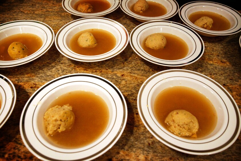 Multiple bowls of matzo ball soup at a Passover seder