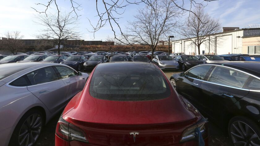 In this Dec. 18, 2018, photo Tesla vehicles sit in a parking lot in Chicago. Shares of electric car