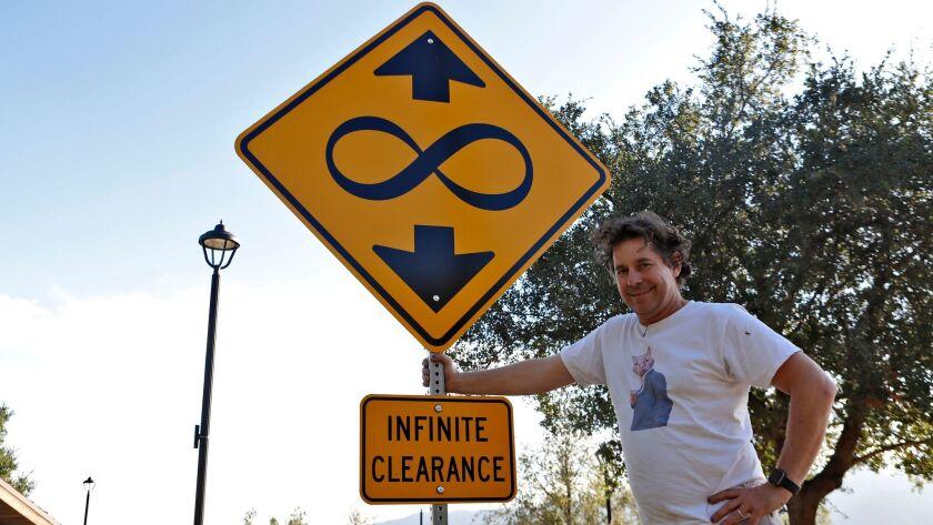 "Artist Scott Froschauer stands next to his ""Infinite Clearance"" street sign artwork at Deukmejian Wi"