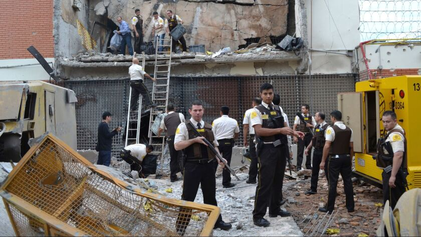 Guards and police inspect a vault that the assailants blew up early morning in Ciudad del Este, Para