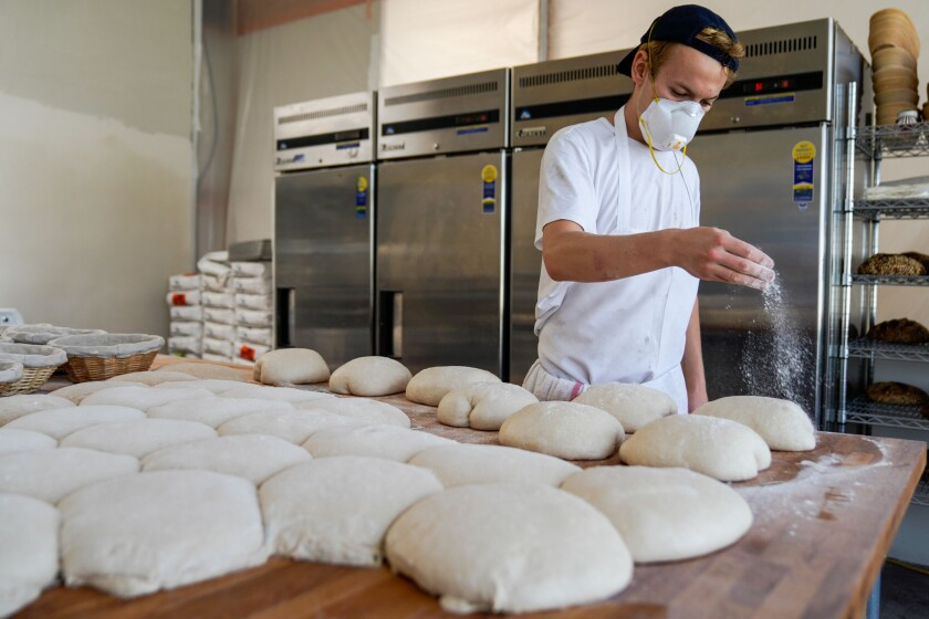 Jyan Isaac Horwitz sprinkles flour on dough