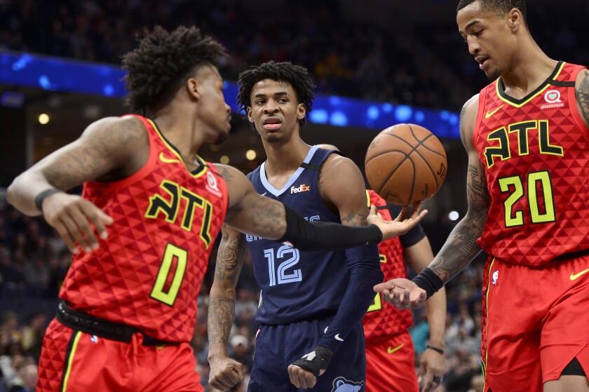 Memphis Grizzlies guard Ja Morant (12) reacts between Atlanta Hawks guard Brandon Goodwin (0) and forward John Collins (20) after scoring in the second half of an NBA basketball game Saturday, March 7, 2020, in Memphis, Tenn. (AP Photo/Brandon Dill)