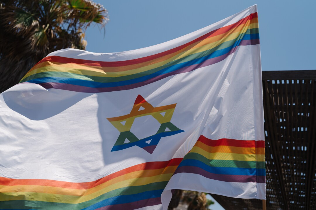A Pride-themed Israeli flag is raised above the crowd of parade attendees .