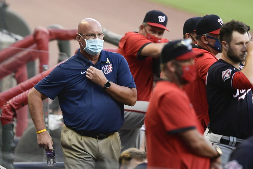 Washington Nationals general manager Mike Rizzo, left, looks on from the dugout during a game against the Atlanta Braves