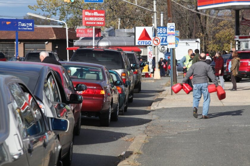 A motorist carries gas cans past a line of cars waiting for gas at a Citgo station in Hackensack, N.J.
