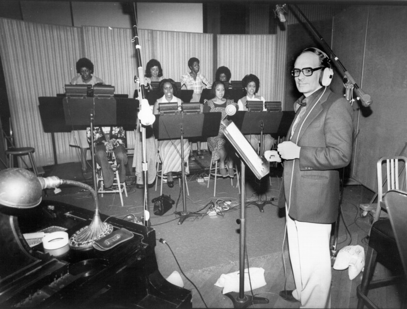 "Ennio Morricone stands in front of a choral group recording in an L.A. studio for the ""Exorcist II: The Heretic"" in 1977"