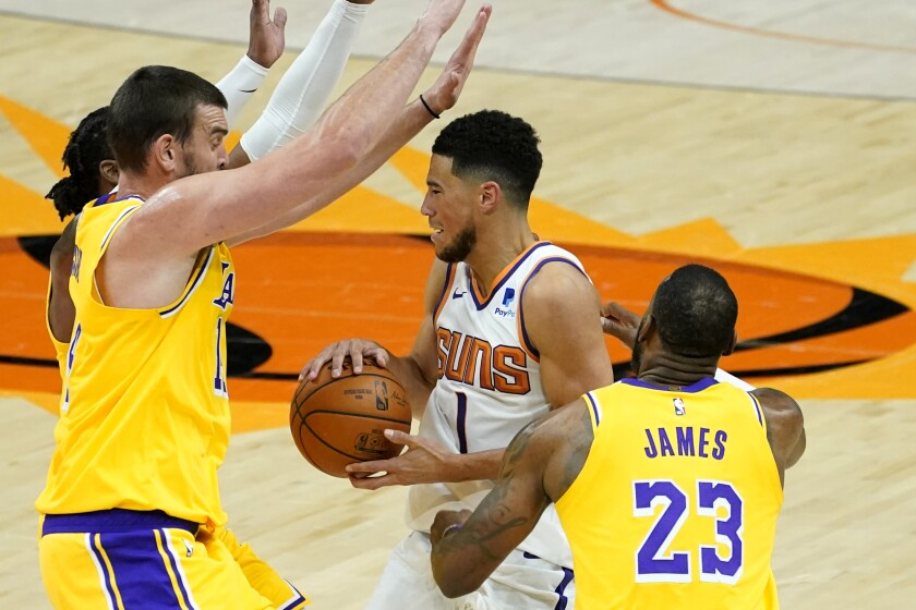 Lakers center Marc Gasol, left, and forward LeBron James pressure Suns guard Devin Booker during a drive on Dec. 18, 2020.