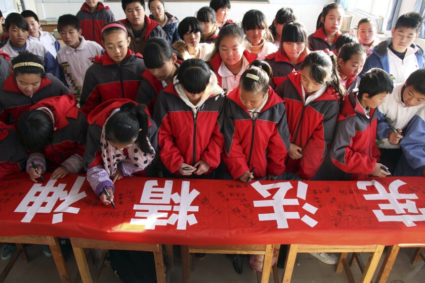 """Students sign a banner with the words """"Constitution spirit"""" at a Dec. 4 event marking China's first Constitution Day in a school in Binzhou city in Shandong province."""