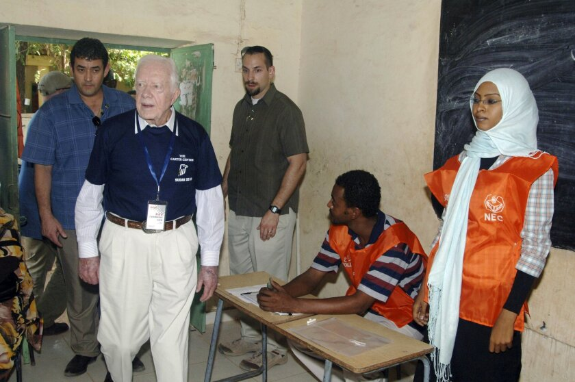 FILE - In this April 11, 2010 file photo, former U.S. President Jimmy Carter, front left, observes a polling station for Sudan's first multiparty elections in decades in Khartoum. Afflicted by cancer, former President Jimmy Carter won't be present for Myanmar's watershed election Sunday. But the ce