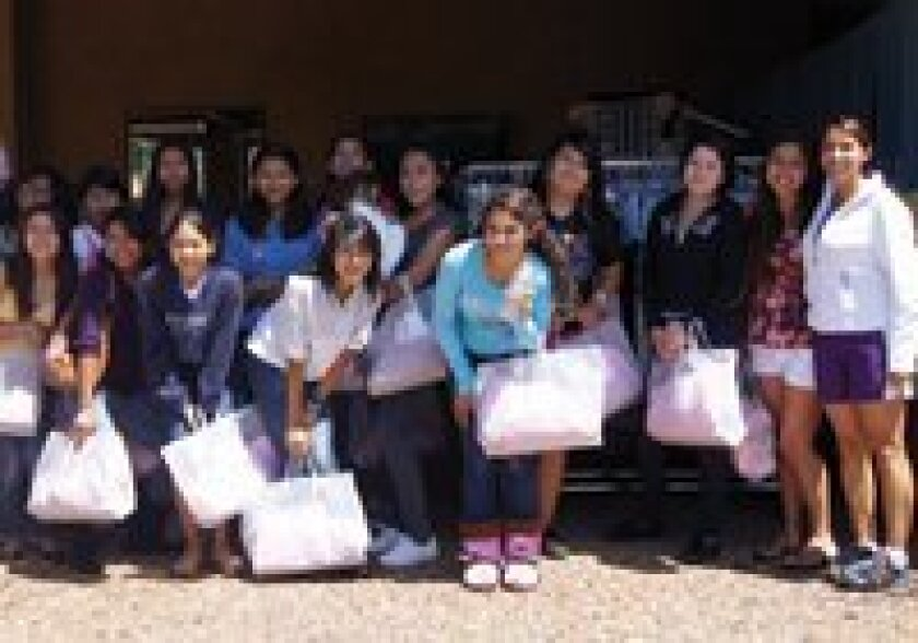 Girls celebrate their new clothes after the 2011 Fitting In event.