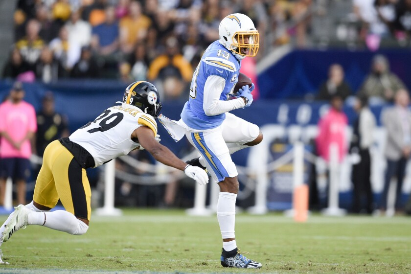 Chargers wide receiver Keenan Allen, right, makes a catch while under pressure from Pittsburgh Steelers free safety Minkah Fitzpatrick during the first half  Sunday in Carson.