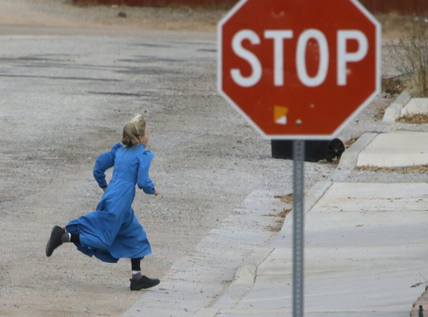 In this Dec. 16, 2014 photo, a girl runs past a street sign in Hildale, Utah. The sister cities of Hildale and Colorado City, Ariz., once run by polygamist leader Warren Jeffs, are split between loyalists who still believe he is a victim of religious persecution and defectors who are embracing gove