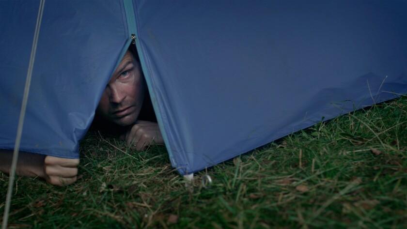 "Leif Edlund peeks out through the flap of a tent in the movie ""Koko-di Koko-da."""