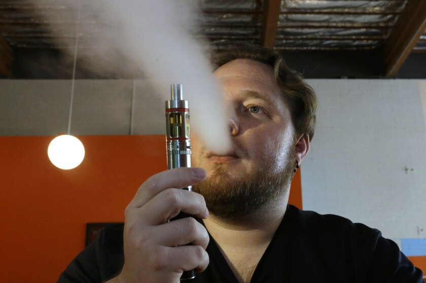 FILE - In this July 16, 2015 file photo, Bruce Schillin, 32, exhales vapor from an e-cigarette in Sacramento, Calif. In 2015, the rate of smoking among adults in the U.S. fell to 15 percent due to the biggest one-year decline in more than 20 years, according to a report by the Centers for Disease Control and Prevention released on Tuesday, May 24, 2016. The increased popularity of electronic cigarettes has likely played a role, but it is not yet clear whether this will help further propel the decline in smoking, or contribute to an increase in smoking in years to come. (AP Photo/Rich Pedroncelli, File)