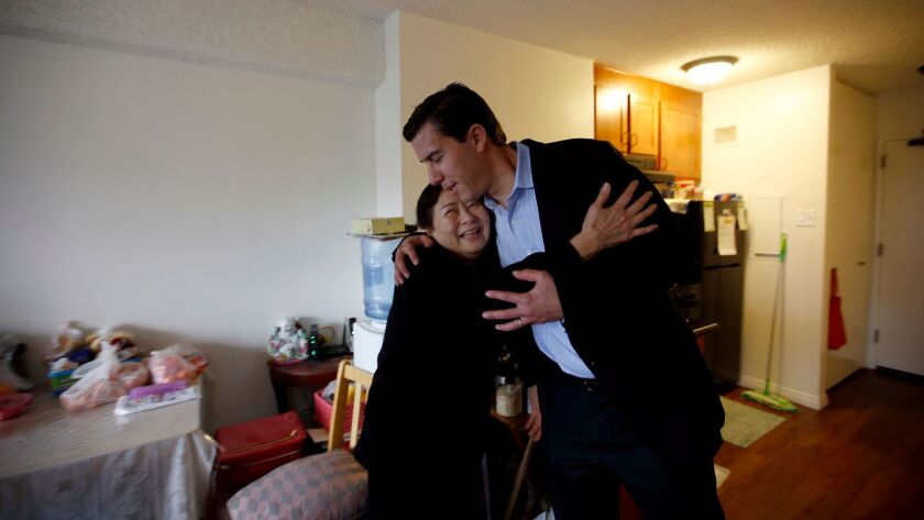 Zenaida Jose, 67, left, hugs Jordan Pynes, the president of Thomas Safran & Associates, in her Wilshire Towers apartment.