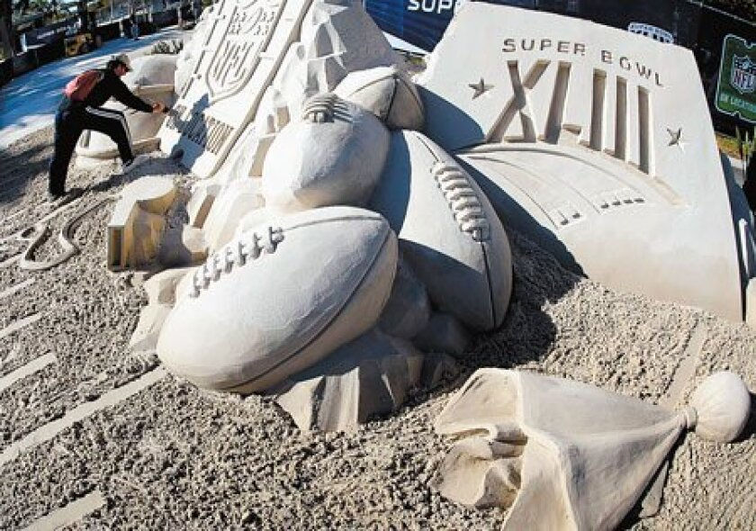 For today's Super Bowl, Stephen Schomaker works on a giant sand sculpture outside Raymond James Stadium in Tampa. (Eric Gay / Associated Press)