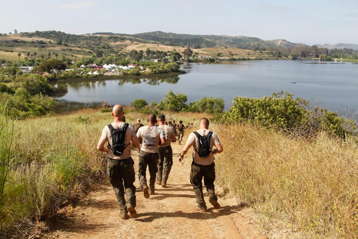 SAN DIEGO, CA June 9th, 2017   Participants run down a steep hill with Lake O'Neill in the background as they compete in the annual Marine Corps Mud Run on Friday morning at Camp Pendleton, California.   (Eduardo Contreras / San Diego Union-Tribune)