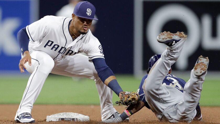 Padres shortstop Allen Cordoba tags out the Brewers' Orlando Arcia on an attempted steal of second base during the eighth inning of a baseball game Tuesday, May 16, 2017, in San Diego.