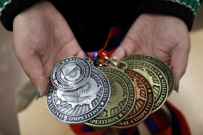 Tamara Cruz shows a few of the nine medals she won at the U.S. Academic Decathlon in Bloomington, Minn.
