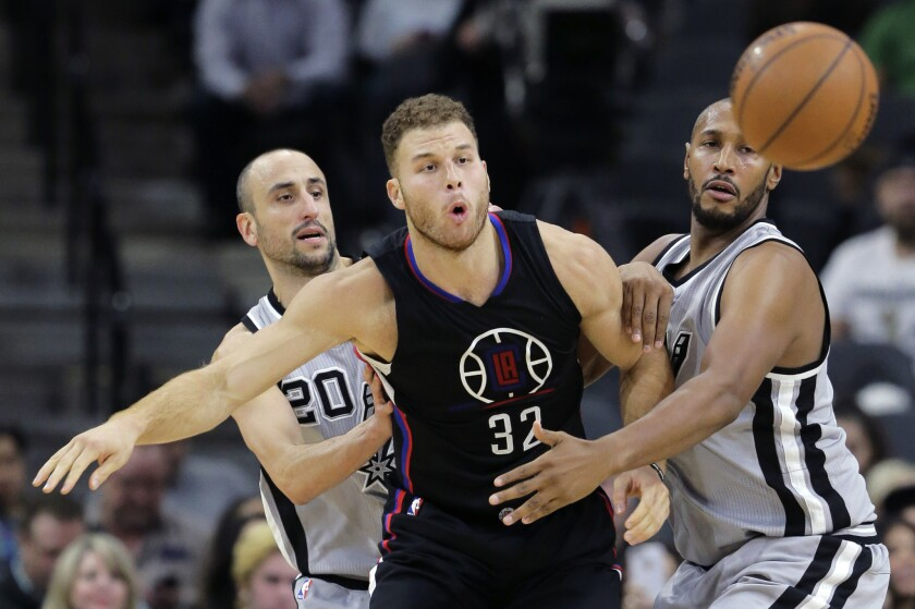 Clippers forward Blake Griffin passes the ball as he is pressured by San Antonio Spurs guard Manu Ginobili, left, and center Boris Diaw on Dec. 18.