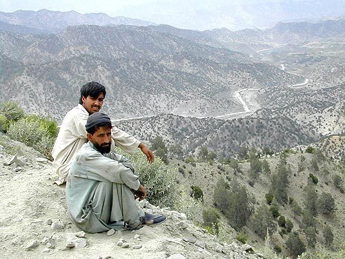 REMOTE TERRAIN: Afghan men sit on a bluff overlooking the road linking Gardez and Khowst. U.S. troops were determined to secure key checkpoints along the road that were used by warlords for extortion. Two detainee deaths linked to a Green Beret unit from Alabama came as a consequence of efforts to pacify the route.