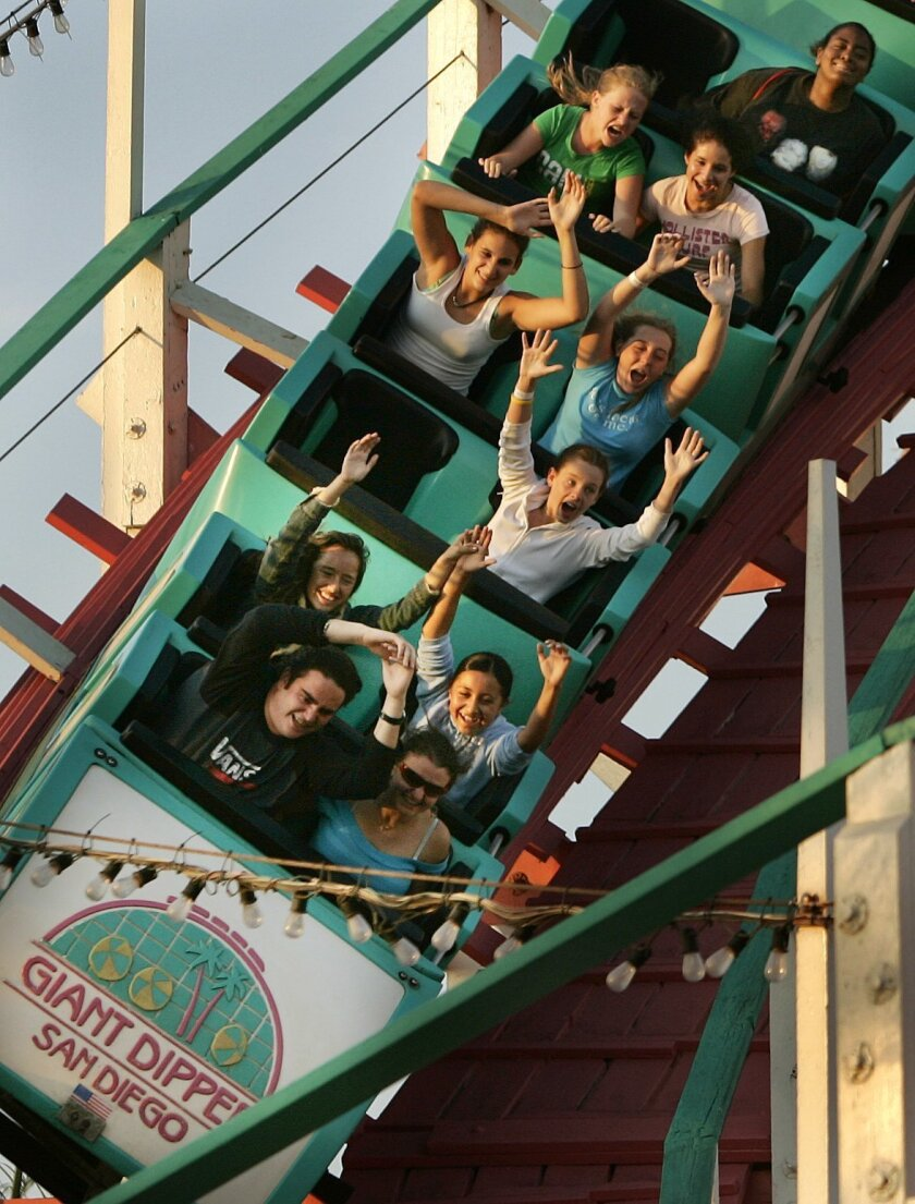 Riders on the Giant Dipper at Belmont Park in Mission Beach plunge down a turn.