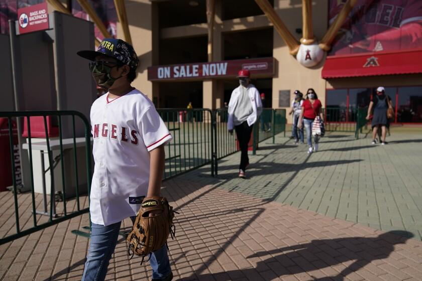 Los fanáticos se marchan del Angel Stadium, tras anunciarse la posposición del juego del sábado 17