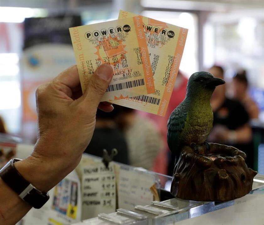 Un hombre muestra sus billetes de lotería Powerball en una tienda. EFE/Archivo