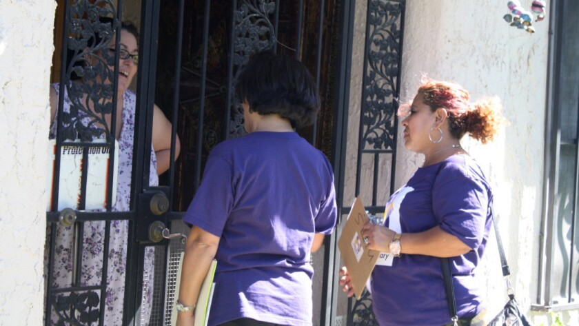 SEIU Executive Vice President Rocio Sáenz and janitor Dora Diaz of Los Angeles speak with Claire Voss, 47, of Las Vegas at her home.