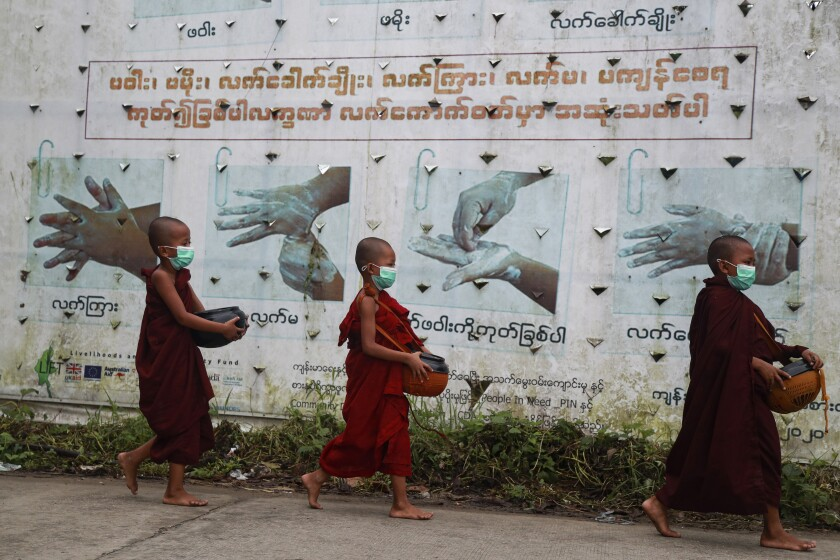 Buddhist novice monks wearing face masks walk past a COVID-19 awareness sign as they collect morning alms Thursday, July 15, 2021, in Yangon, Myanmar. (AP Photo/Thein Zaw)